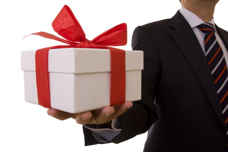 a businessman offering a gift to you (selective focus)